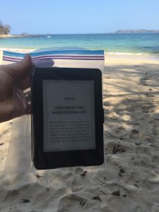 Reading Kindle beach sand