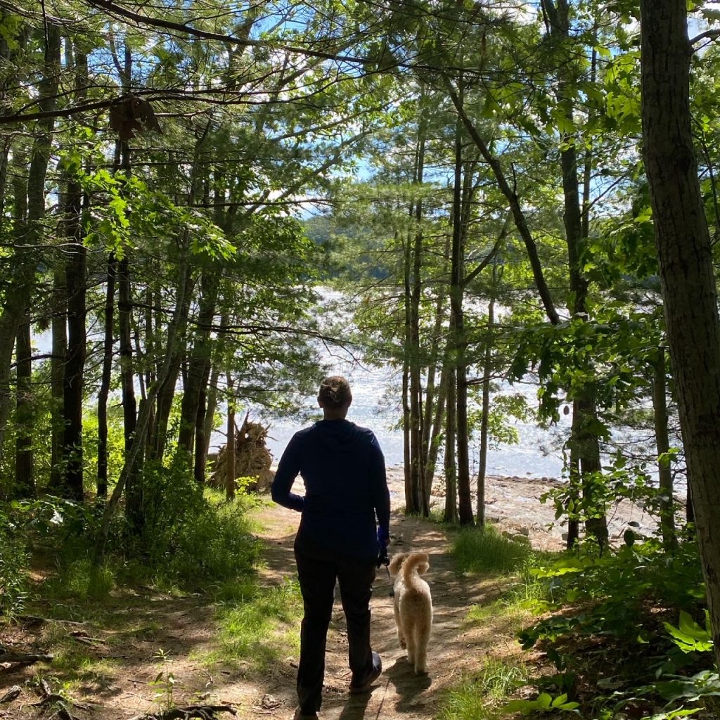 woman dog hiking waterfront